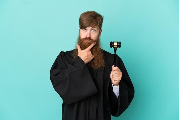 Redhead caucasian judge man isolated on blue background thinking