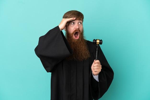 横を見ながら驚きのジェスチャーをしている青い背景に分離された赤毛の白人裁判官の男