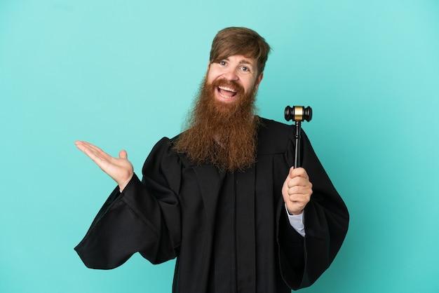 来るように誘うために手を横に伸ばして青い背景に分離された赤毛の白人裁判官の男