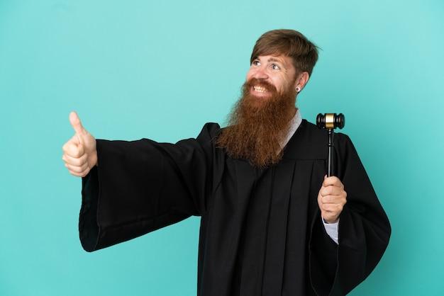親指を立てるジェスチャーを与える青い背景で隔離赤毛白人裁判官男