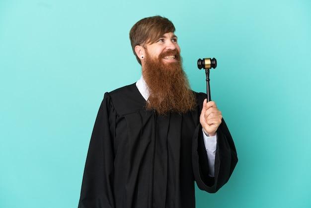 横を向いている青い背景に分離された赤毛の白人裁判官の男
