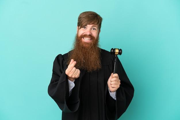 お金のジェスチャーを作る青い背景に分離された赤毛の白人裁判官の男