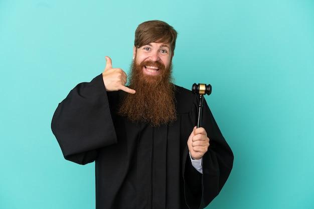 電話ジェスチャーを作る青い背景に分離された赤毛の白人裁判官の男。コールバックサイン
