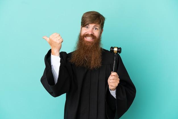 製品を提示する側を指している青い背景に分離された赤毛の白人裁判官