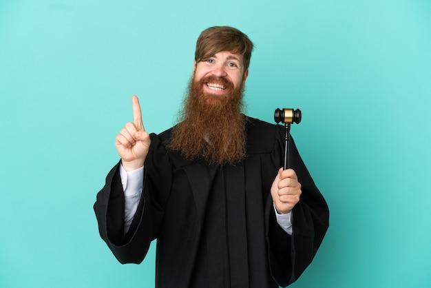最高の兆候を示して指を持ち上げて青い背景に分離された赤毛の白人裁判官の男