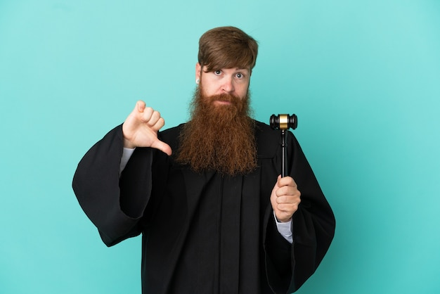 否定的な表現で親指を示す青い背景に分離された赤毛の白人裁判官の男