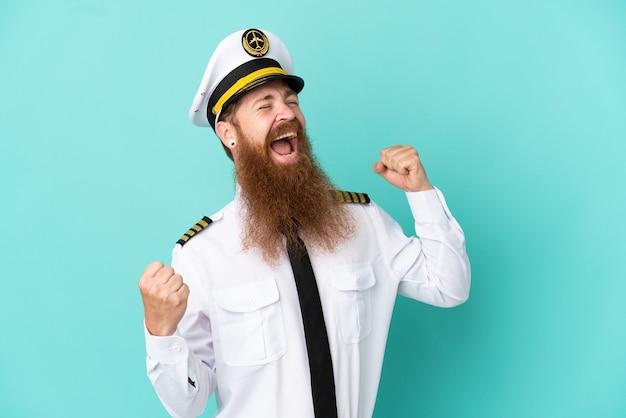 승리를 축하하는 노란색 배경에 고립 된 럭비를하는 빨간 머리 백인 남자