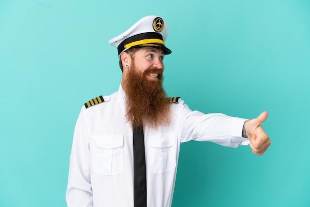 親指を立てるジェスチャーを与える黄色の背景に分離されたラグビーをしている赤毛の白人男性