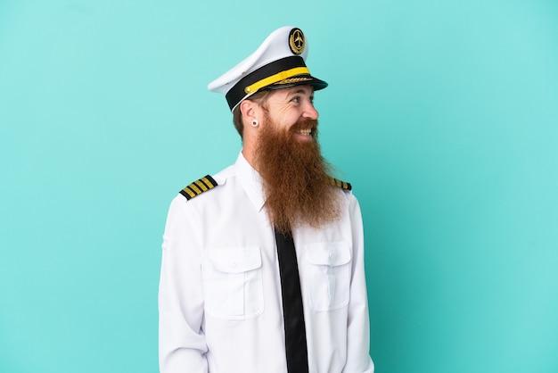 노란색 배경에 격리된 럭비를 하고 옆을 바라보며 웃고 있는 빨간 머리 백인 남자
