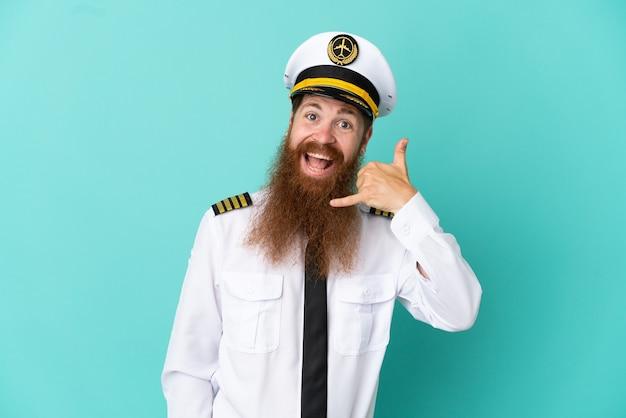 電話のジェスチャーを作る黄色の背景に分離されたラグビーをしている赤毛の白人男性。コールバックサイン