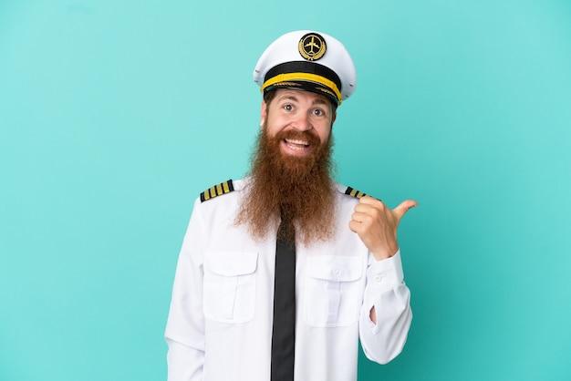 製品を提示する側を指している黄色の背景に分離されたラグビーをしている赤毛の白人男性
