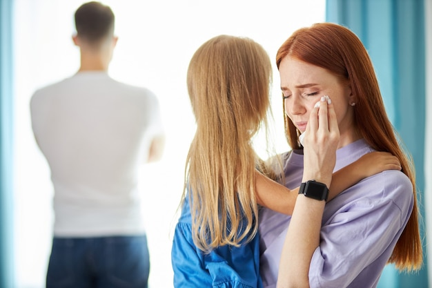 Redhead caucasian woman with child girl leaves man as he turned away