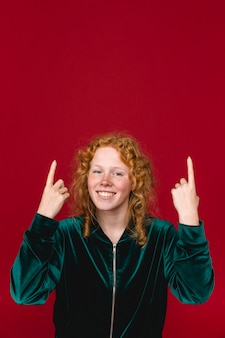 Redhead cheerful young woman pointing up