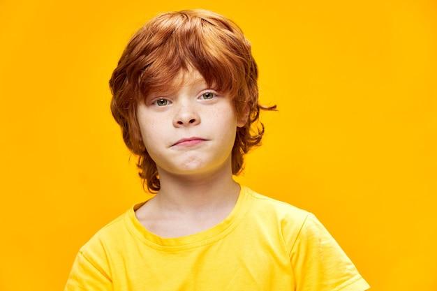 빨간 머리 아이 얼굴 가까이 노란색 티셔츠와 재미 어린 시절 격리 된 배경