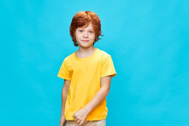 빨간 머리 아이 미소 노란색 티셔츠 스튜디오 파란색 배경
