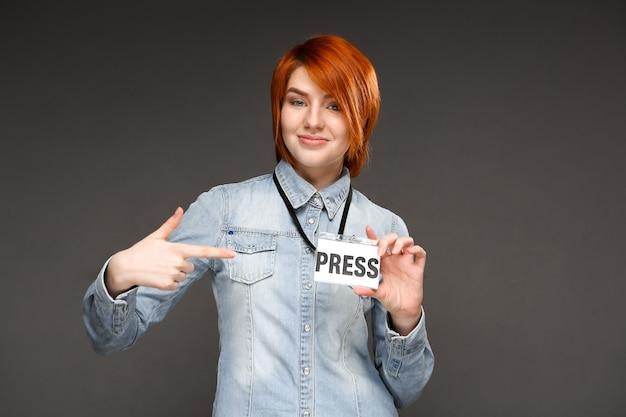 Redhead confident journalist show her press badge
