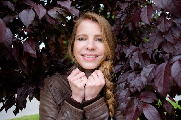 Redhead cute woman in purple leaves portrait