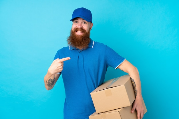 Redhead delivery man over isolated blue wall and pointing it