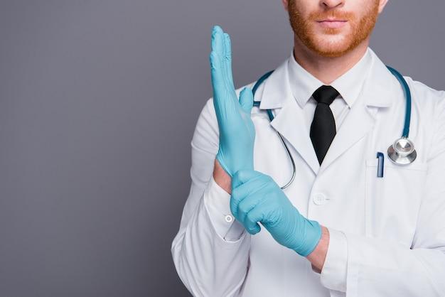 灰色の壁にポーズをとって白衣を着た赤毛の医者