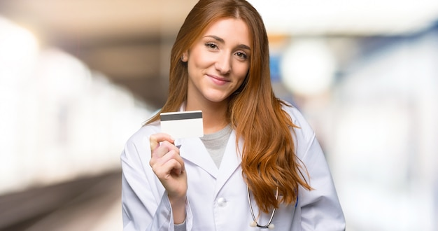 Redhead doctor woman holding a credit card in the hospital