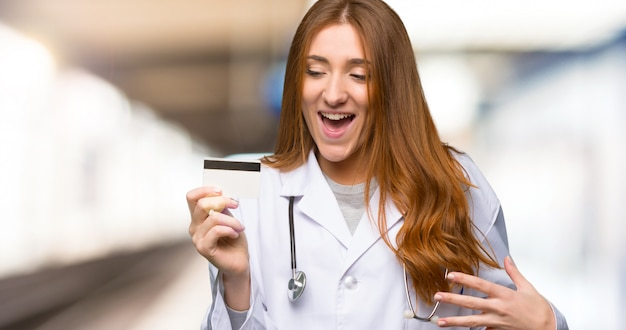 Redhead doctor woman holding a credit card and surprised in the hospital