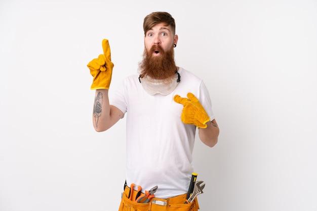 Рыжий электрик человек с длинной бородой на белом фоне с удивленным выражением лица