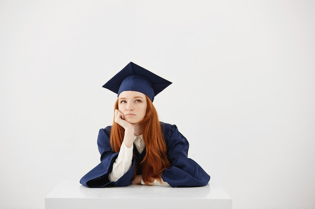 Redhead female graduate in mantle thinking sitting over white surface