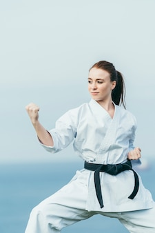 Redhead female karate athlete preparing to attack with punch