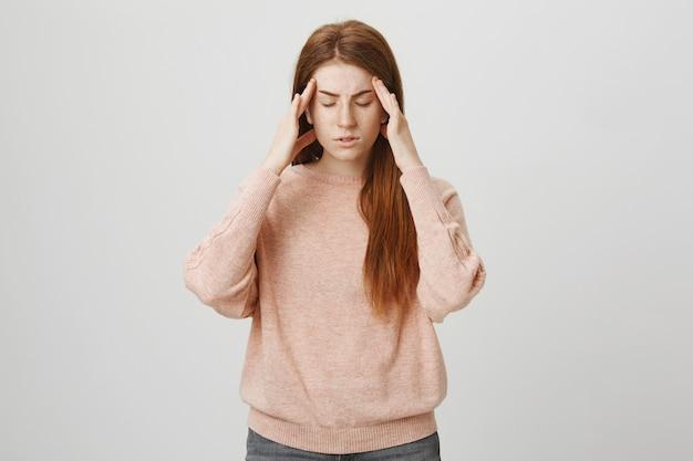 Redhead female student having headache, suffer migraine