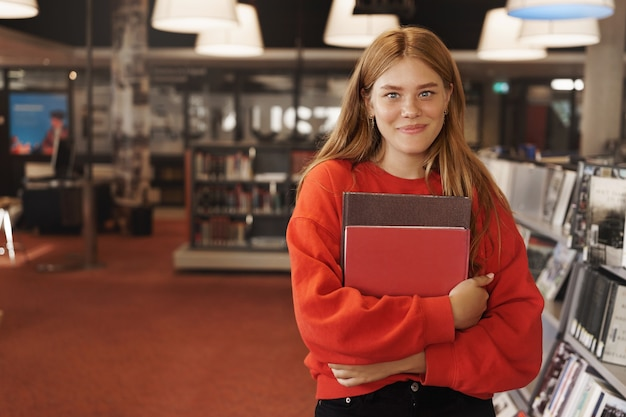Redhead female studying, holding books in bookstore and smiling.