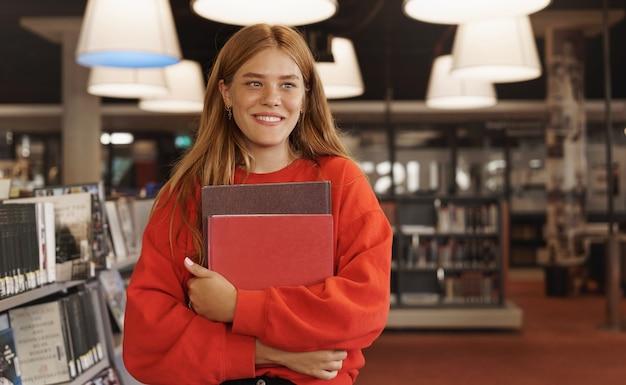 Рыжая женщина учится, держа книги в книжном магазине и улыбается.