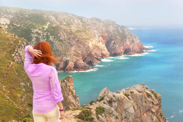ロカ岬に立っている赤毛の女性旅行者と大西洋、シントラ、ポルトガルを参照してください