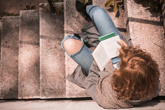 Redhead female with opened book on stone stair