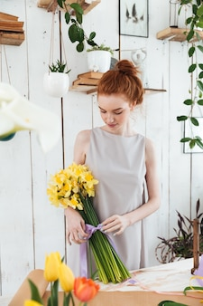 Redhead florist bandaging flowers with violet ribber
