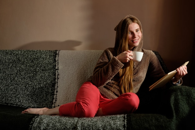 Redhead ginger girl in funny hoody reading book, drinking coffee, lying on the sofa and smiling