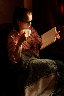 Redhead ginger girl in stripped shirt reading book, drinking coffee, lying on the sofa and smiling