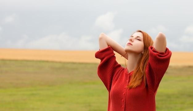 Рыжая девушка на лугу возле поля пшеницы