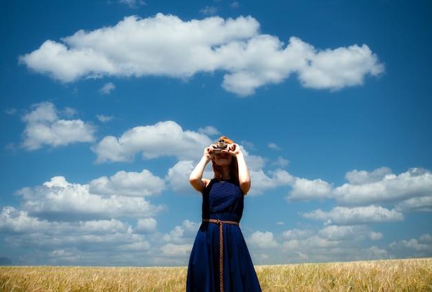 Рыжая девушка в весеннем поле с ретро камерой.
