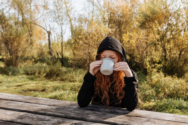 Redhead girl on an autumn picnic drinks tea from a mug.