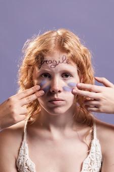 빨강 머리 소녀는 단어와 페인트로 덮여