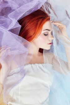 Redhead girl dreams, bright makeup, clean skin, facial care. redhead girl in a light air colored dress lies on the floor, a portrait close-up. romantic woman with long hair and cloud dress