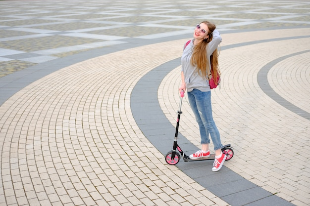 Redhead girl dressed in grey hoody, blue jeans and red sneakers riding kick scooter near modern building