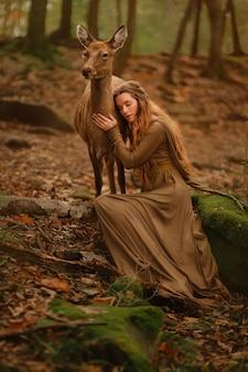 Рыжая девушка в длинном платье в лесу с оленями