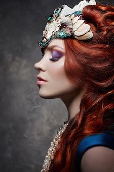 빨간 머리 소녀 멋진 외모, 파란색 긴 드레스, 밝은 메이크업 및 큰 속눈썹. 붉은 머리를 가진 신비한 요정 여자. 큰 눈과 채색 된 그림자, 긴 속눈썹. 섹시한 모습, 공주