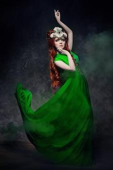 赤毛の女の子の素晴らしい表情、緑のロング ドレス、明るいメイクと大きなまつげ。赤い髪の謎の妖精女