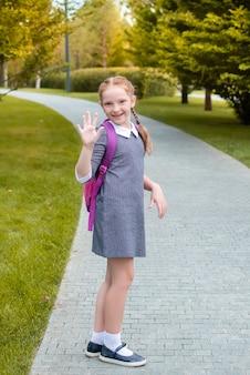 Рыжая девушка идет учиться. машут и улыбаются в парке.