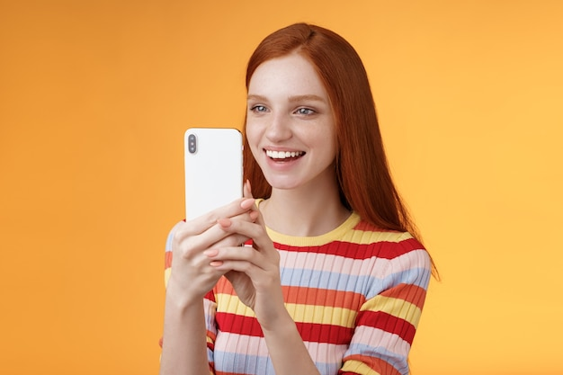 Redhead girl having fun recording hilarious friend actions hold smartphone look display amused shooting funny video telephone standing orange background satisfied smiling delighted. lifestyle