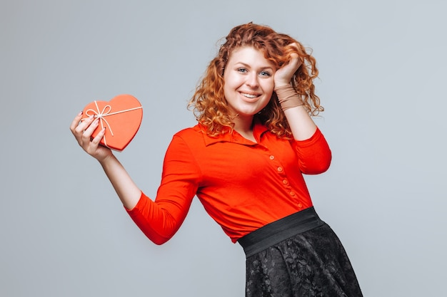 Redhead girl holding gift heart box