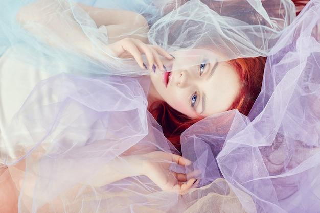明るい色のドレスを着た赤毛の少女が床に横たわっている