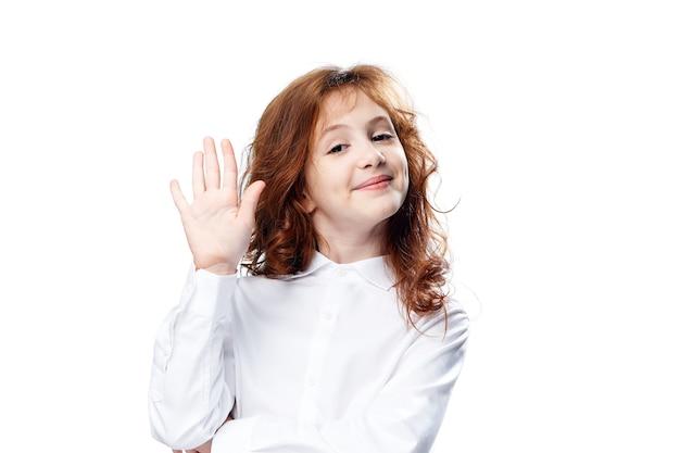 シャツを着た赤毛の女の子が分離に手を振ります。高品質の写真